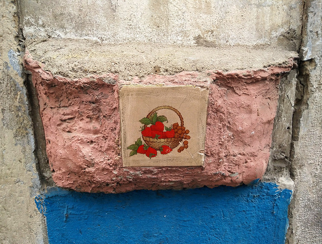 Ada Wanders/Włóczykijada. The tile with a picture of a basket with fruits on the wall in Alfama in Lisbon.